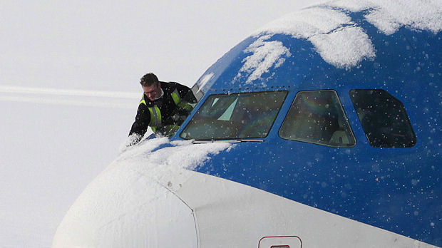 An engineer clears the nose of a snow covered plane at Edinburgh airport, Scotland