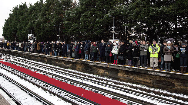 Commuters wait in the snow for a tube train at Parsons Green station in London