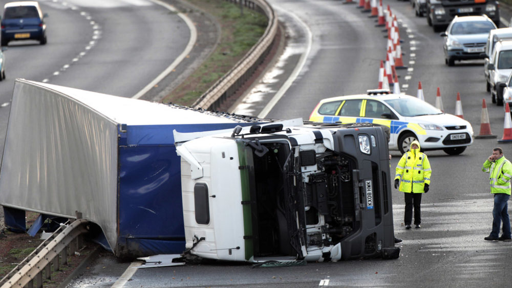 People stand next to a truck blown over in high winds on the A720 city bypass in Edinburgh. AA Insurance has reported 200 per cent more calls than would normally be expected at this time of year.