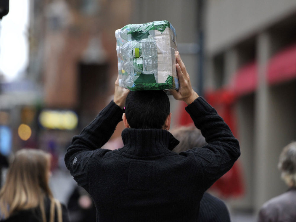 A man carries a case of water down Lexington Avenue in midtown in New York as stores begin to close down in preparation for Hurricane Sandy. (Getty)