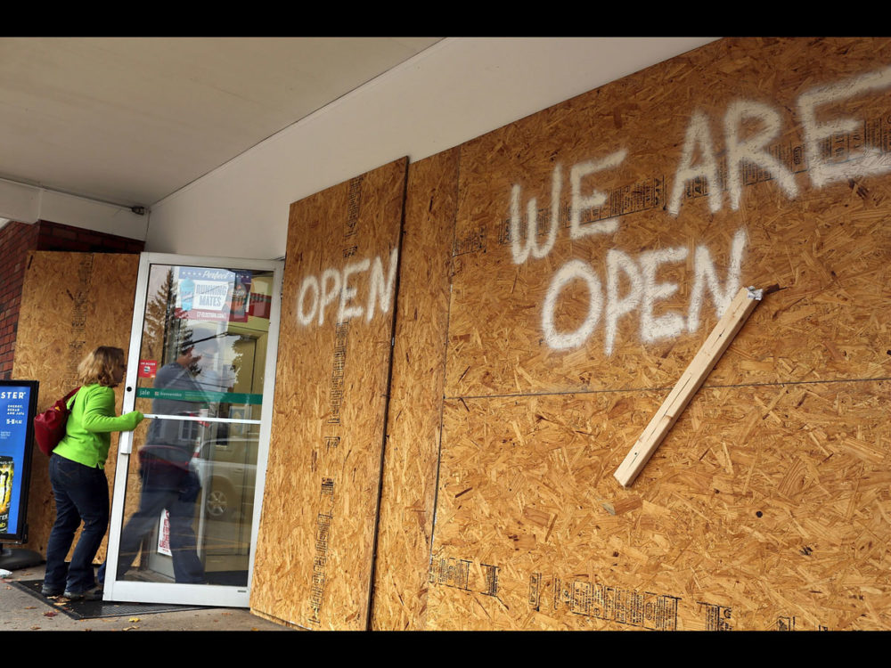 A boarded-up store remains open for business as the first signs of Hurricane Sandy approach in Fairfield, Connecticut. (Getty)