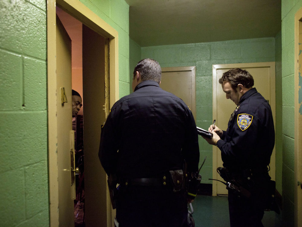 New York City police officers go door to door in a housing project to take note of which residents are ignoring the mandatory evacuation order in Queens. (Reuters)