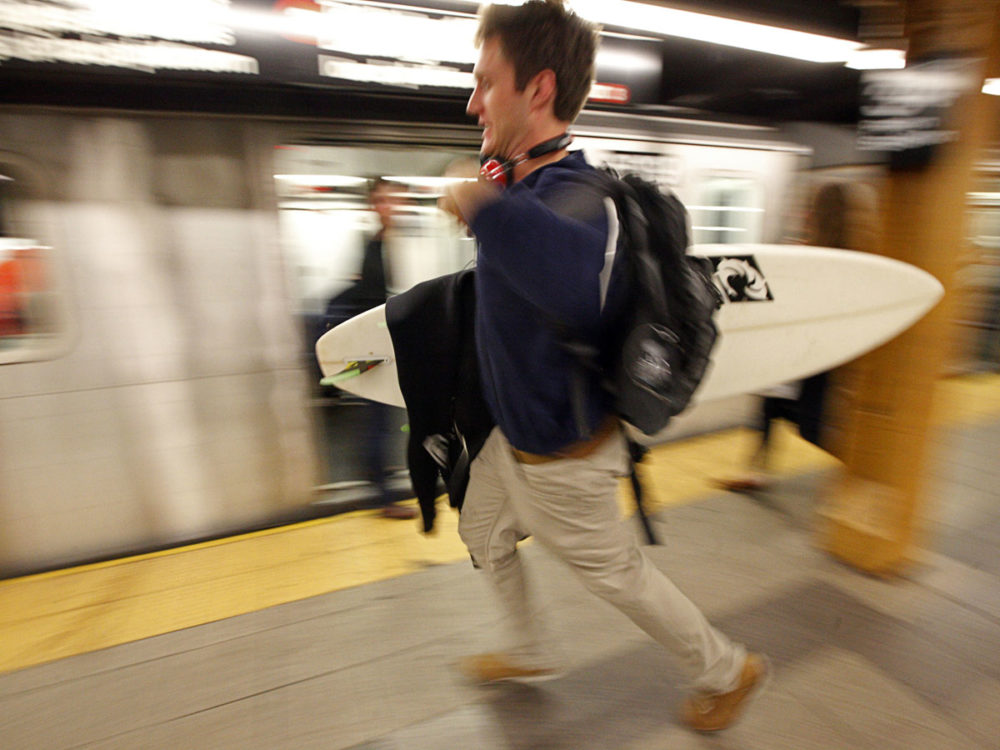 A surfer rushes to board one of the final subway trains in New York. Governor Andrew Cuomo announced that New York City will close its bus, subway and commuter rail service Sunday evening. (Reuters)