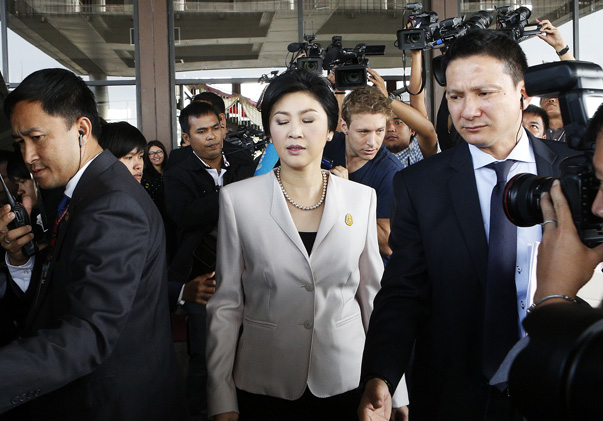 Thai PM Yingluck is escorted to her car after a news conference in Bangkok