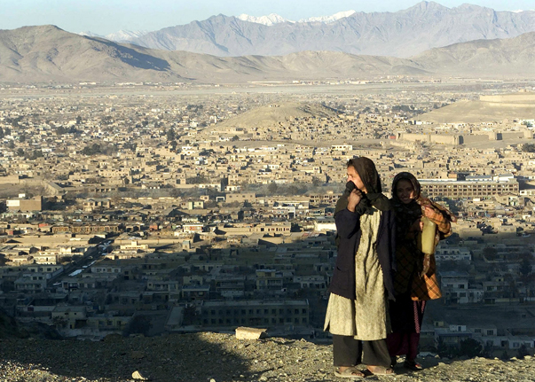 Two Afghan girls look out from a hill over the post-war Afghan capital of Kabul  January 18, 2002. T..