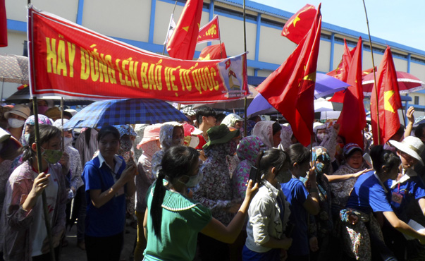 Workers wave Vietnamese national flags during an anti-China protest at a Chinese shoe factory in Vietnam's northern Thai Binh province