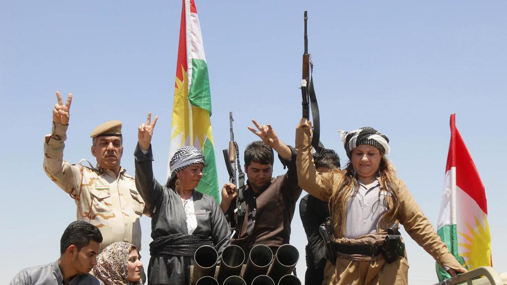 Members of the Kurdish Peshmerga celebrate in the city of Kirkuk