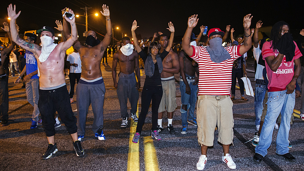 Demonstrators gesture with their hands up after protests in reaction to the shooting of Michael Brown turned violent near Ferguson, Missouri