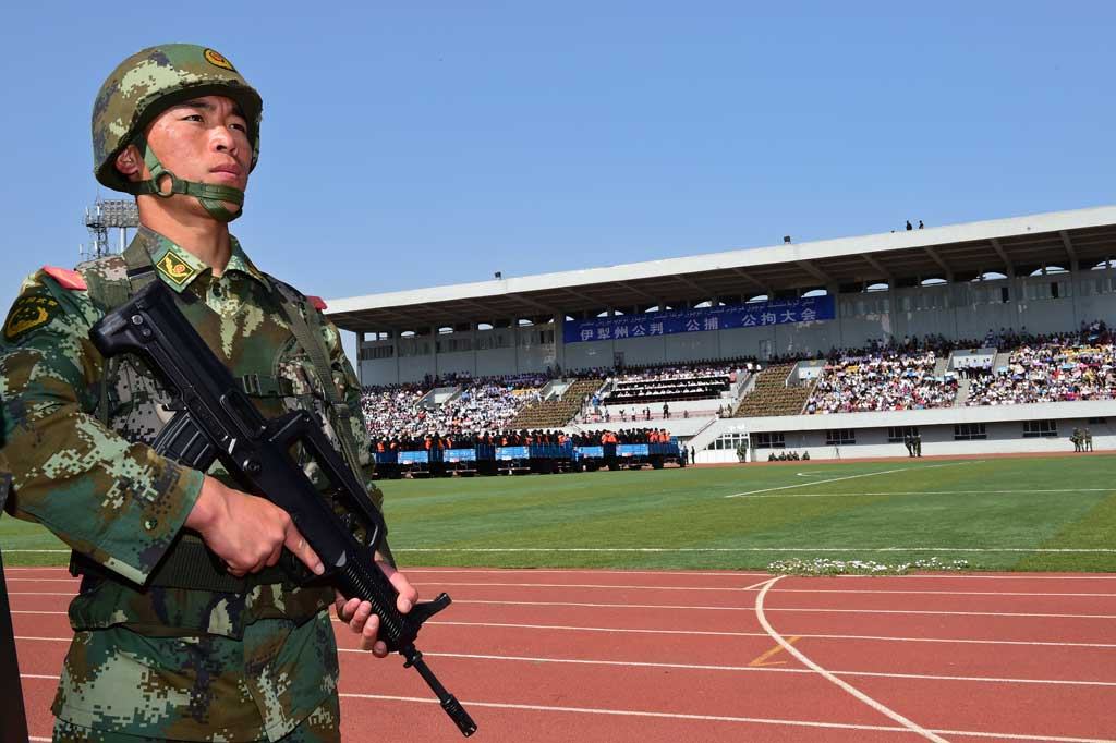 A paramilitary policeman stands guard near trucks carrying criminals and suspects during a mass sentencing rally at a stadium in Yili, Xinjiang Uighur Autonomous Region May 27, 2014