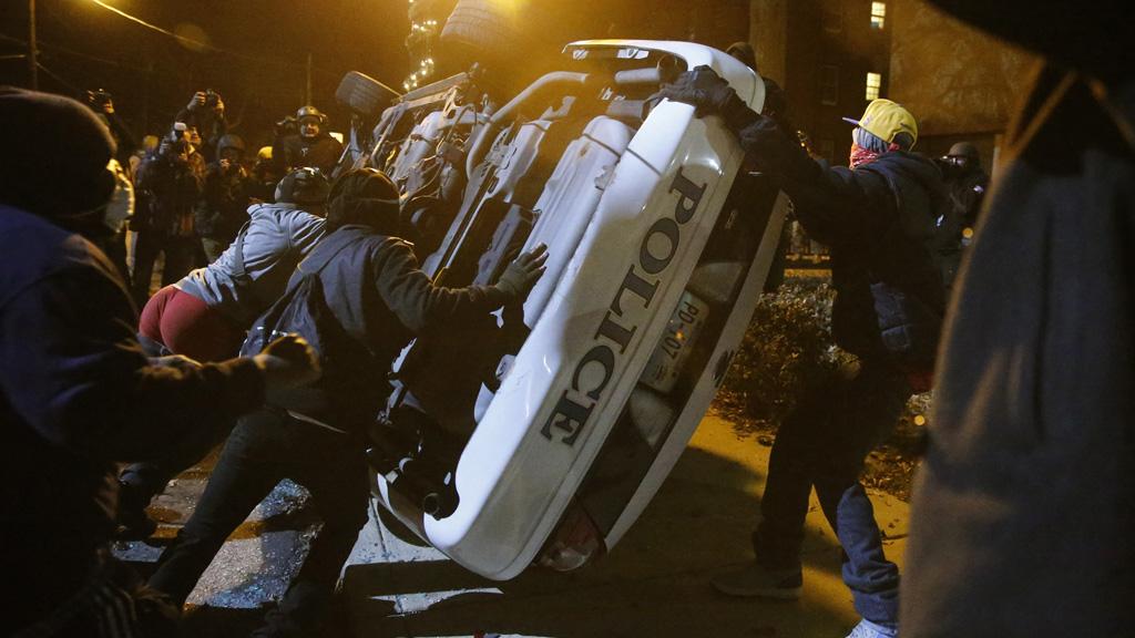 Protesters flip over a Ferguson police car in Ferguson