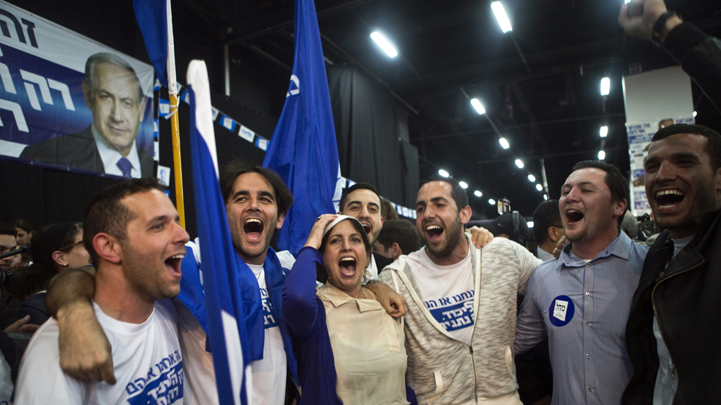 Likud party supporters react after hearing exit poll results in Tel Aviv