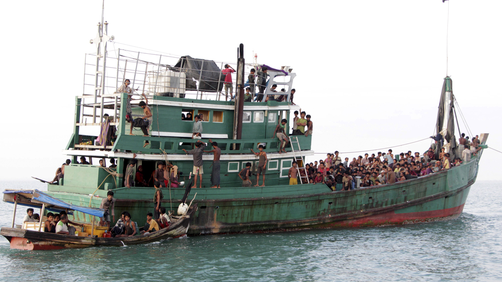 Rohingya and Bangleshi migrants wait on board a fishing boat before being transported to shore, off the coast of Julok