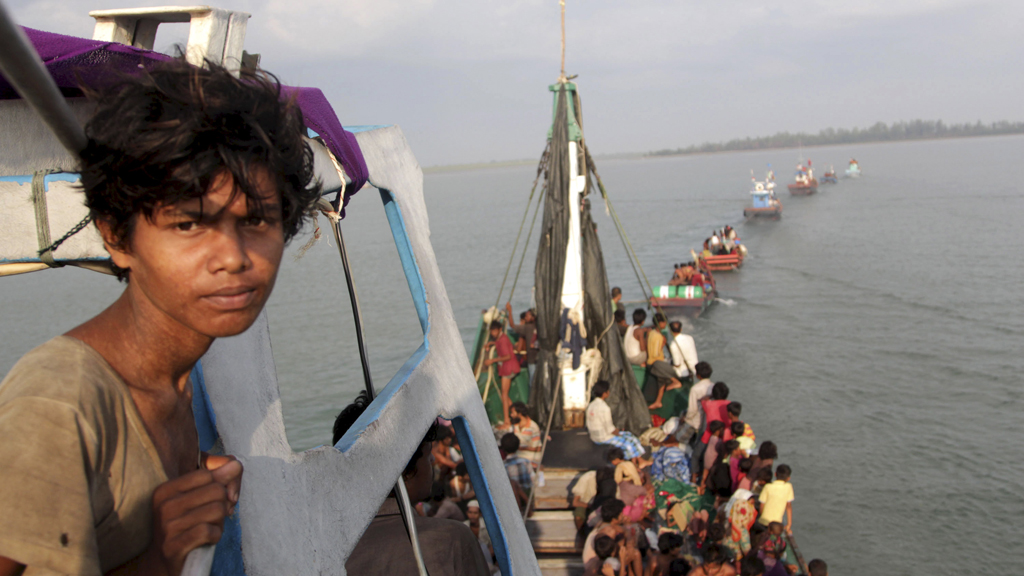 A fishing boat carrying Rohingya and Bangleshi migrants is pulled to shore by Achenese fisherman off the coast of Julok