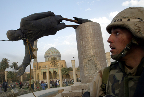 FILE PHOTO - A U.S. soldier watches as a statue of Iraq's President Saddam Hussein falls in central Baghdad, Iraq April 9, 2003. PREUTERS/Goran Tomasevic/File Photo - RTX2JY55