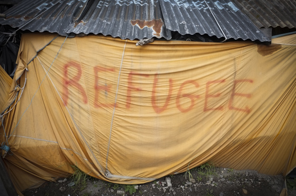 "A makeshift tent with the word ""refugee"" seen in the The Jungle Calais. June 2015."