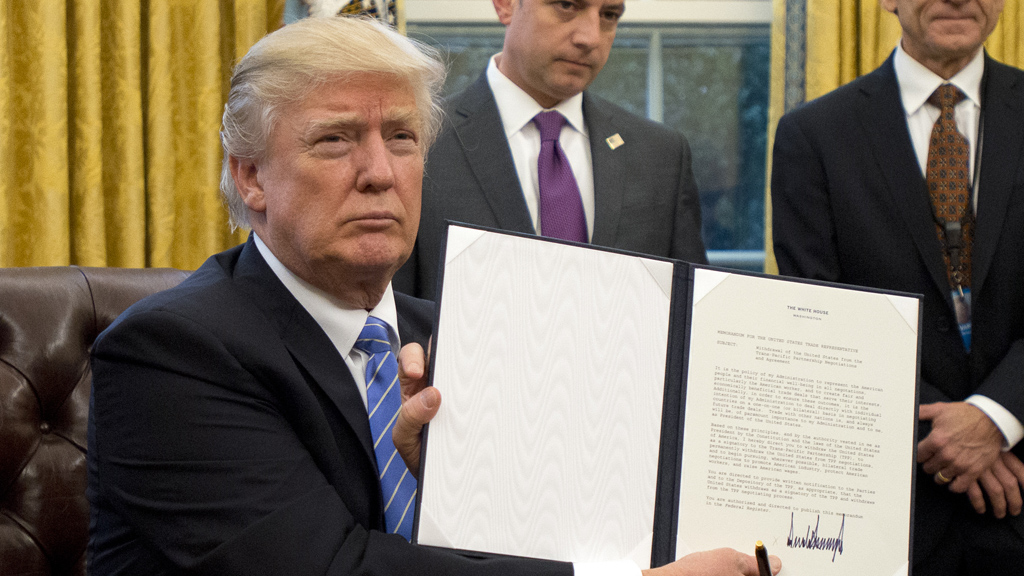 "WASHINGTON, DC - JANUARY 23: (AFP OUT) U.S. President Donald Trump shows the Executive Order withdrawing the US from the Trans-Pacific Partnership (TPP) after signing it in the Oval Office of the White House in Washington, DC on Monday, January 23, 2017. The other two Executive Orders concerned a US Government hiring freeze for all departments but the military, and ""Mexico City"" which bans federal funding of abortions overseas. (Photo by Ron Sachs - Pool/Getty Images)"