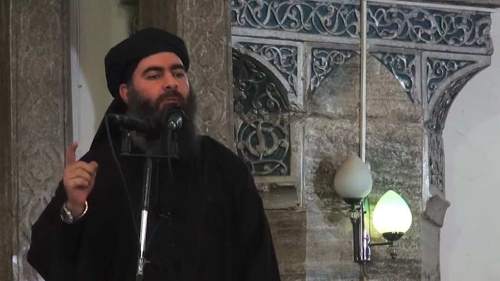 "This July 5, 2014 photo shows an image grab taken from a propaganda video released by al-Furqan Media allegedly showing the leader of the Islamic State (IS) jihadist group, Abu Bakr al-Baghdadi, aka Caliph Ibrahim, adressing Muslim worshippers at a mosque in the militant-held northern Iraqi city of Mosul. Baghdadi, who on June 29 proclaimed a ""caliphate"" straddling Syria and Iraq, purportedly ordered all Muslims to obey him in the video released on social media. In early 2014 the self-styled Islamic State entered the northern Syrian city of Raqqa, declaring it their capital and beginning a reign of terror marked by grisly public executions. Armed sharia police patrolled the streets as ""enemies"" of the regime were crucified or decapitated, their severed heads impaled on spikes in the city square. Student Abdalaziz Alhamza and his friends decided to form ""Raqqa is Being Silently Slaughtered"" (RBSS), a band of courageous citizen journalists who risk their lives to document IS atrocities. / AFP / - (Photo credit should read -/AFP/Getty Images)"